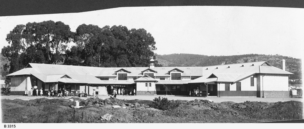 1926. The newly completed school buildings stand in open space in front of a stand of large gum trees and a view of the hills. This is possibly the opening day of the school as there appears to be both parents and children attending, wearing their 'Sunday best' clothes. In the foreground some children play on builder's rubble. State Library of South Australia