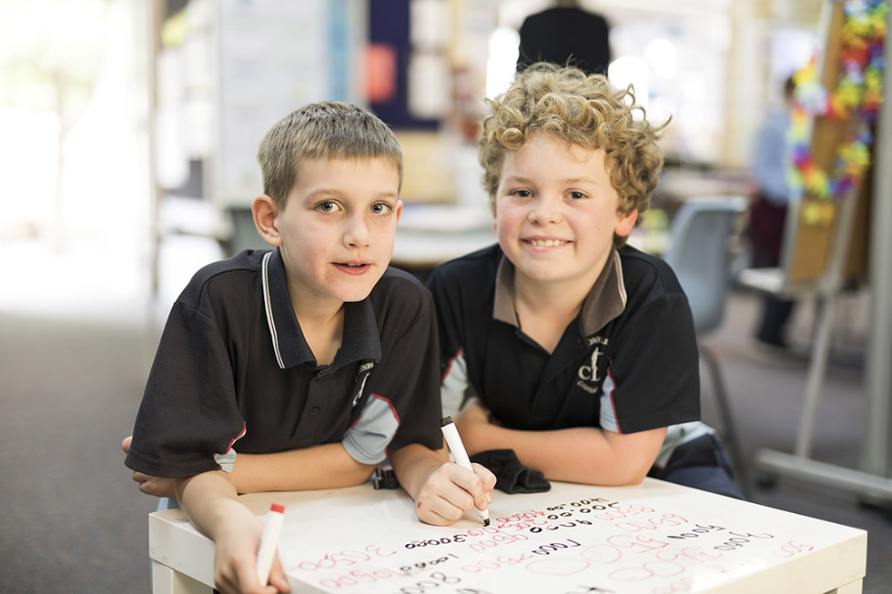Two young students working at desk and smiling