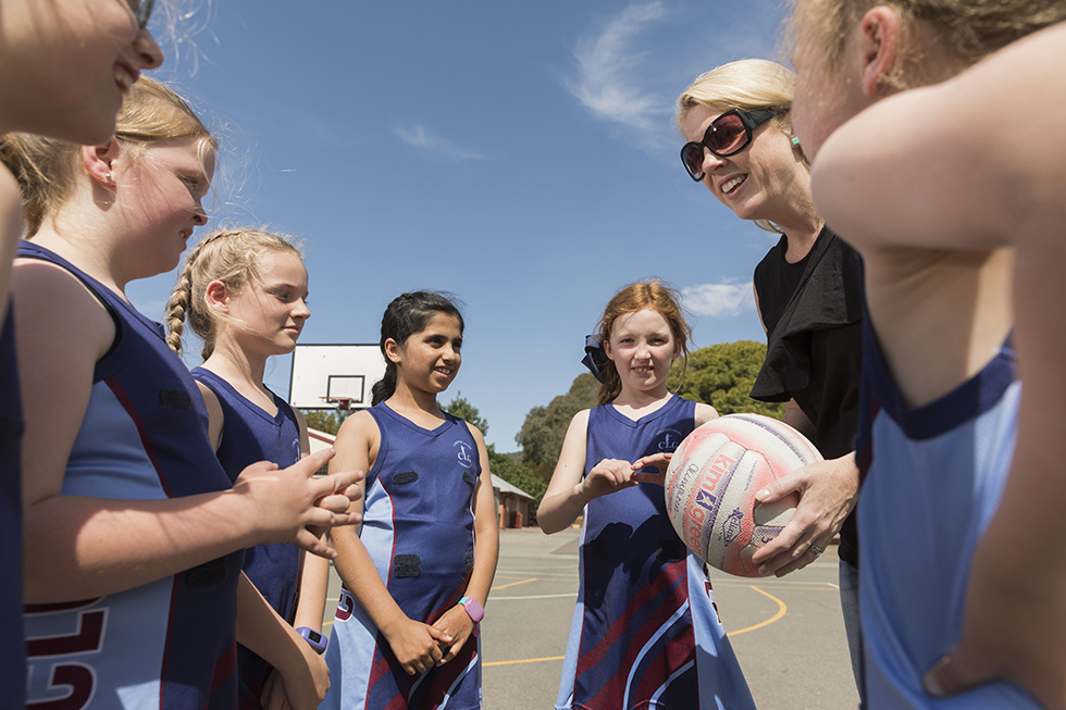 Children in netball clothing with their coach