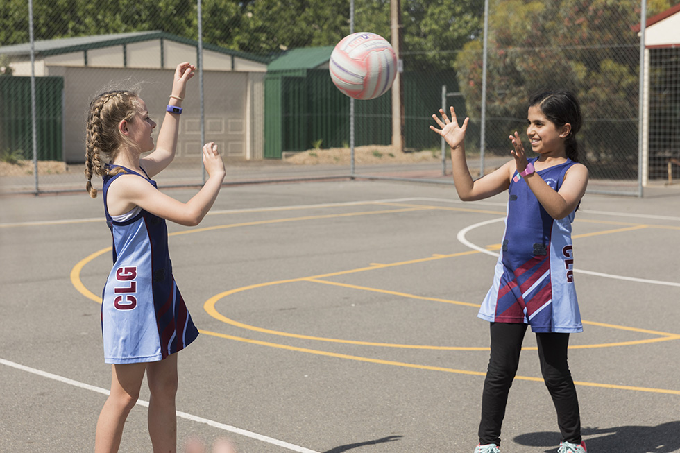 Two children playing netball