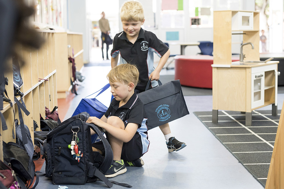 Two children in school polo shirts, navy shorts, with school bags.