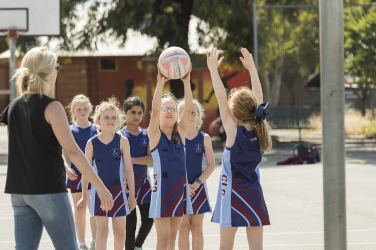 Parent volunteer with students playing netball
